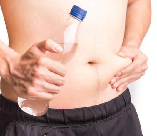 man pinching belly, holding water bottle, water retention
