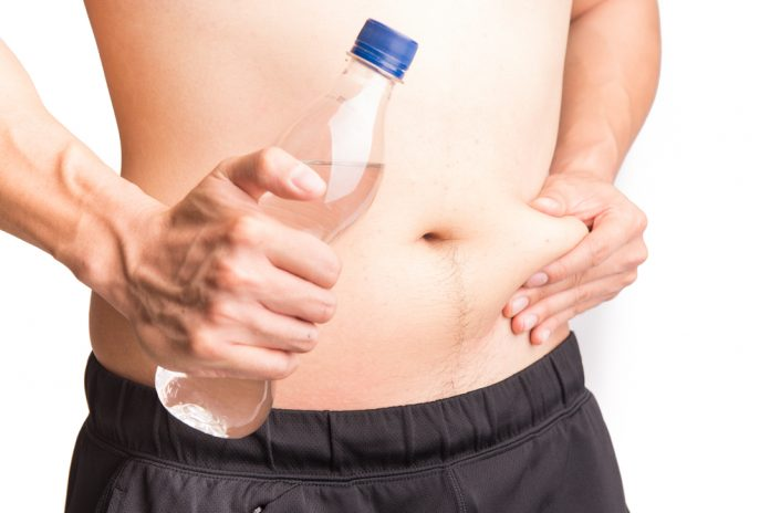 man pinching belly, holding water bottle, water retention