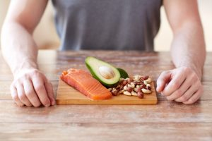 man with paleo food on wooden board