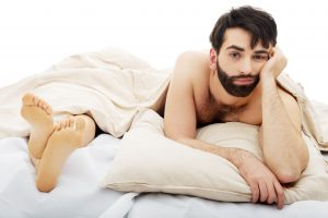 frustrated man in bed while partner sleeps opposite him