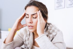 woman with headache massaging temples