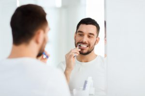 man brushing teeth in front of bathroom mirror