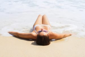 woman sun bathing on the beach