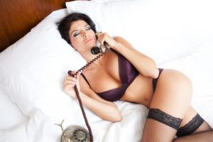 woman in lingerie in bed talking on phone, booty call