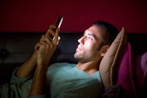 man using cellphone at night read