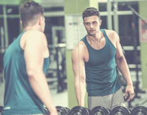 man looking at his reflection on the gym mirror
