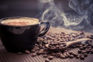 steaming cup of coffee with coffee beans on table