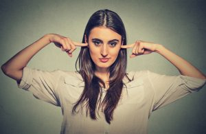 woman covering ears with index fingers and smirking refuse to listen