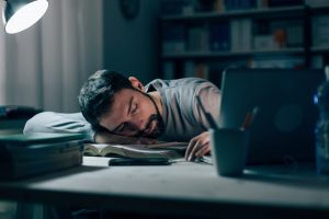 tired man falling asleep on work desk