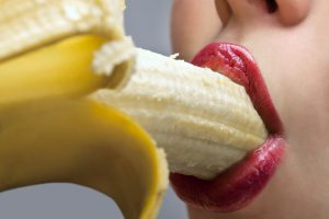 woman sucking at a banana