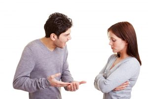 man being angry and aggressive towards woman bowing her head