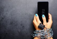 woman's hands chained to phone addiction to social media and tech