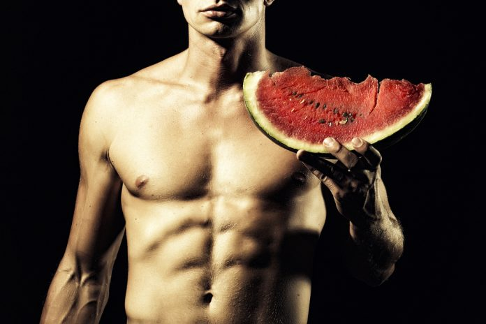 ripped man holds watermelon