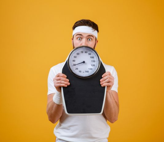 fitness guy holds weighing scale