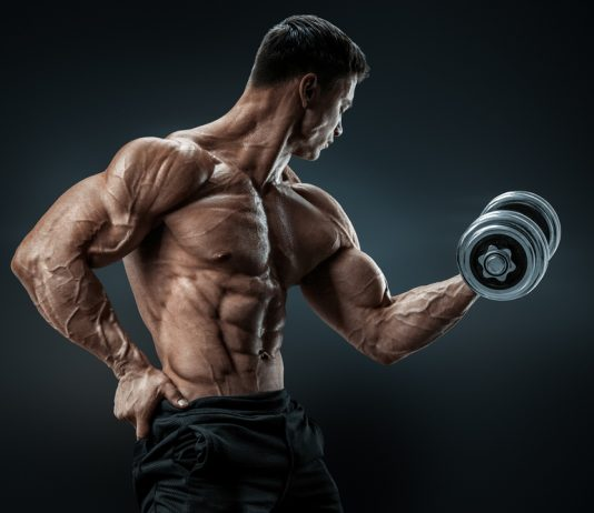 ripped guy pumping muscles